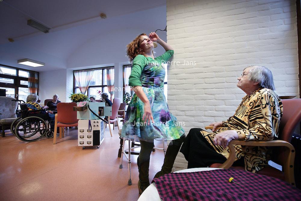 Nederland, Amsterdam , 27 oktober 2009..Mobiel platform Zona's Kiosk genaamd van de Stichting Kunst in de Zorg hier aan het werk in Sint Jacobsverzorgingstehuis..Zona's Kiosk is een reizend platform met kunst voor ouderen in zorgcentra..Op de foto zien we kunstenares Iena Stochem in innige houding dansend met een van de  ouderen van het Zorgcentrum. Mobile platform Zonas' Kiosk of the Art In Care Foundation at work in St. Jacobs home for the elderly.