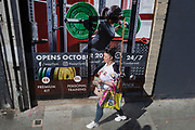 A woman smokes a cigarette as she walks past an ad for a forthcoming easyGym in Camberwell, south London, on 29th August 2019, in London, England.