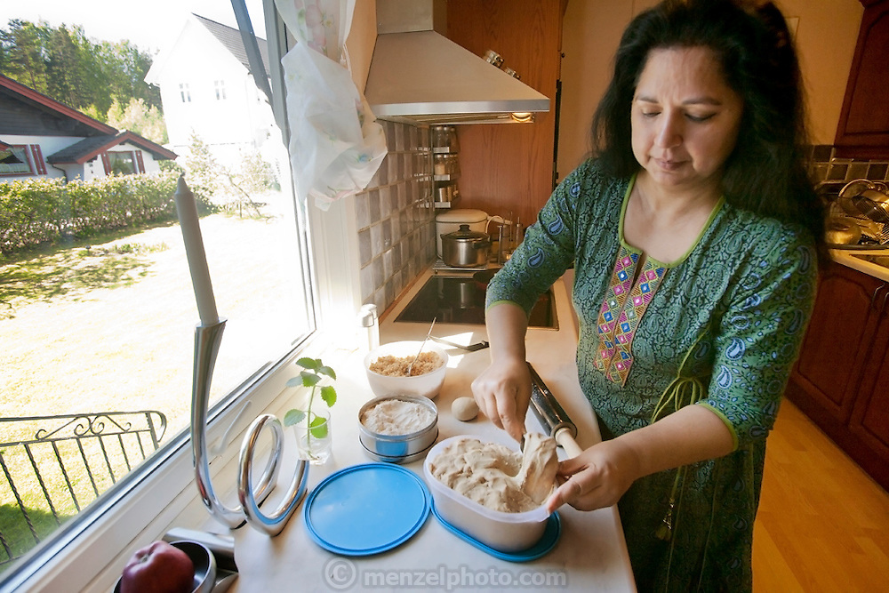 The Qureshi family of Lorenskog, Norway, an Oslo suburb. Pritpal Qureshi, 49, preparing chapati, unleavened flat bread, in her kitchen. Model-Released.