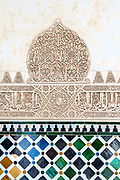 Carved Muslim inscroption and tilework in the Alhambra, Granada, Spain