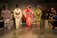 Taking a Bow at the Kimono Show at Nishijin Textiles; Kimono are made of silk and normally very expensive though there is now a thriving market in second hand kimono. Nowadays they are worn at formal or traditional occasions such as funerals, weddings or tea ceremonies. Kimono differ in style and color depending on the occasion on which it is worn and the age and marital status of the person wearing it. To put on a kimono needs some practice. Especially tying the belt (obi) alone is difficult so that many people require assistance. Wearing a kimono properly includes proper hair style, traditional shoes, socks, underwear, and a small handbag for women.