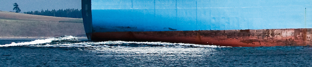 The aft end of a cargo ship needing paint maintenance  arriving is making a wake in Puget Sound, Washington, USA