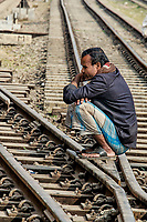Crossroads: A man squats down on a railway line that splits in two, deep in thought and given his demeanour, the choice of route seems to mimic his dilemma, Dhaka Bangladesh.