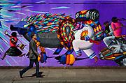 Pedestrian walking past graffiti wall on construction hoarding in Great Eastern Street East London.