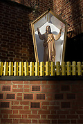 An effigy of Jesus Christ encased in a shrine box outside a Catholic church in Camberwell, south London. Encased in a glass-sided box and behind what resembles yellow garden fencing, the Christian idol stands with outstretched arms, a traditional figure for Catholics to practice idolatry. The church walls are constructed from red brick, in a style much-seen in industrial buildings.