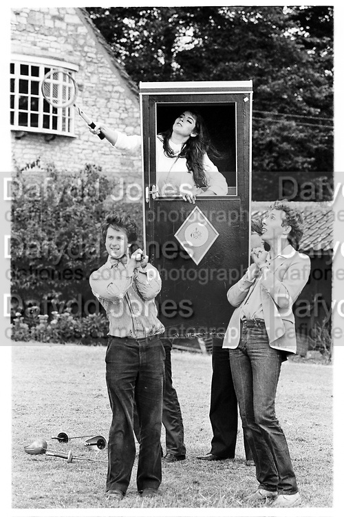 Nigella Lawson playing tennis from a sedan chair, supported by Hugo Spowers and Jerome Fack. Dangerous Sports club tea party. Dutch ambassador's house. Gloucestershire. 22 July 1981. © Copyright Photograph by Dafydd Jones 66 Stockwell Park Rd. London SW9 0DA Tel 020 7733 0108 www.dafjones.com