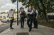 Police wearing face masks observe as activists play drums in Canonbury Road, nearby Highbury and Islington Station, on Thursday, Oct 1, 2020 to mark the 'National Tree Killing Day' outside the Dixon Clark Court development plan. (VXP Photo/ Sabrina Merolla)