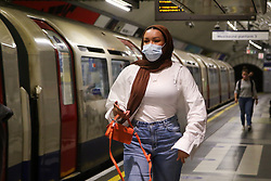 © Licensed to London News Pictures. 13/07/2021. London, UK. A woman wearing a face covering travelling on the London Underground. In yesterday's press conference, Prime Minister Boris Johnson announced that the legal requirement to wear face coverings on public transport will be removed in step four of the government's road map out of lockdown on Monday 19 July. Health Secretary Sajid Javid told the Commons that masks would still be 'recommended' on public transport, but people without a face covering would no longer be fined after restrictions are eased on 19 July. Photo credit: Dinendra Haria/LNP