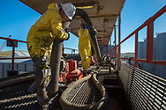 Pedro Michel, left, and Julio Perez, right, both floor hands, work at installing a tube to vacuum out remaining sediment in a storage tank on a Raven Oil Drilling rig near Watford City N.D., Oct 1, 2013. In 2008 the North Dakota oil boom started its ongoing period of extraction of oil from the Bakken formation. Shale gas reserves has given the United States more independence over other nations such as Venezuela and countries in the Middle East.