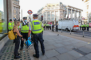 Police officers arrested a climate activist from Extinction Rebellion during the group's 'Impossible Rebellion' series of actions at Oxford Circus in central London, on Wednesday, August 25, 2021. - Climate change demonstrators from environmental activist group Extinction Rebellion continued with their latest round of protests in central London, promising two weeks of disruption. (VX Photo/ Vudi Xhymshiti)