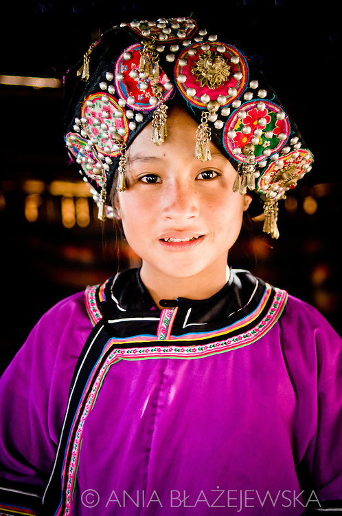 Laos, Muang Sing. Portrait of a young Lolo girl wearing a beautiful traditional headdress. <br /> Lolo is one of the ethnic minorities living in the north of Laos