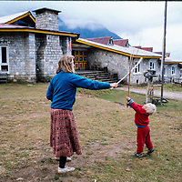 A trekker and her son play outside a trekking hotel at Lukla airstrip in the Khumbu region of Nepal 1986.