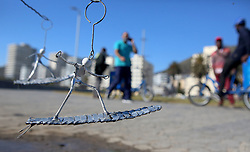 """South Africa - Cape Town - 17 June 2020 - Man selling Handmade sculptures of a surfer as people walk by Along the Sea Point Promenade soaking up the sunlight, and enjoying the warm day following a few rainy days Picture"""" Brendan Magaar/African News Agency(ANA)"""