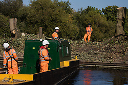 HS2 workers pause tree felling works alongside the Grand Union Canal in connection with the HS2 high-speed rail link due to the arrival of anti-HS2 activists on the other bank of the canal on 21 September 2020 in Harefield, United Kingdom. Anti-HS2 activists continue to try to prevent or delay works for the controversial £106bn HS2 high-speed rail link on environmental and cost grounds from a series of protection camps based along the route of the line between London and Birmingham.