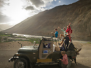 Tourists entering Chipursan valley in a jeep. It is the most Northwestern part of Pakistan, bordering Afghanistan and China. The people speak the Wakhi Language and belong to the Ismaili sect of Islam.