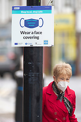 ©Licensed to London News Pictures 29/10/2020  <br /> Sidcup, UK. A lady wearing a face covering near a sign. Coronavirus guidance signs in Sidcup High Street, London. Photo credit:Grant Falvey/LNP