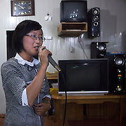 I'm 20, I'm North Korean<br /> <br /> Miss Kim is 20. She lives in Pyongyang, North Korea's display window. She's studying<br /> English. First of her class, she was lucky enough to come with me during my 6th trip to<br /> North Korea as an assistant guide. She had never previously left Pyongyang. It was a<br /> unique opportunity for her to visit her own country and to get to meet and speak to a<br /> foreigner. She was shy at first, but became quite talkative as the days went on, and<br /> describe to me the everyday lives of young North Koreans. Without ever crossing over<br /> the Party line...<br /> Small chats between friends who will never meet again…<br /> <br /> <br /> -Do you know Michael Jackson? -I have heard of him, yes.<br /> -And Lady Gaga?<br /> -I don't know who he is, no...<br /> <br /> -Why doesn't English or American pop music reach your country?<br /> -Mr Eric, because it is not what we like to listen to... But we know Mozart, Bach and Beethoven!<br /> <br /> -Why do boys and girls not dance together?<br /> -They are shy, do you dance with girls that you don't know Mr.Eric?<br /> <br /> -What is the criteria for beauty in North Korea?<br /> -Mr Eric, a woman should have big eyes, a high nose, a small mouth and a white skin, and she should not be skinny. Women in North Korea are truely beautiful flowers.<br /> <br /> -Do women find Kim Jong Un handsome? -Mr Eric, that's an outrageous question.<br /> <br /> -Nobody dyes their hair in North Korea?<br /> -No. We need to respect the haircut regulation, we have a lot of choice! -But don't you want to have the haircut you want?<br /> -No, that's the last thing we're concerned about.<br /> <br /> -Do you have any idea of the lastest European fashions? -No, Mr. Eric.<br /> -Young people buy jeans in which there are holes. -Holes?<br /> -Yes, they buy worn jeans or which have been ripped. -I don't believe you Mr.Eric, you are joking.<br /> <br />  -Do you know the name of this character on the tshirt? -No