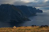 Wild mountain camping on summit of Fuglhuken mountain peak with rugged northern coast of Moskenesøy in background, Lofoten Islands, Norway
