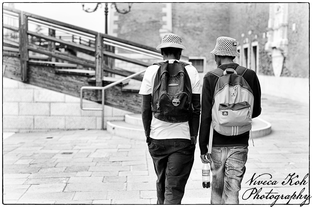 Two men walking towards bridge, Venice, Italy.