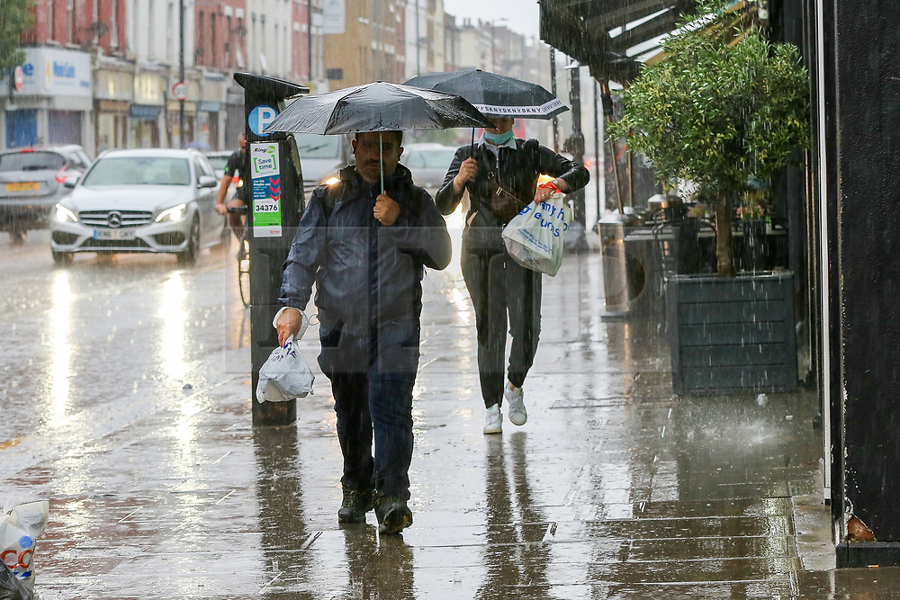 © Licensed to London News Pictures. 18/06/2021. London, UK. Members of public shelter from the rain underneath umbrellas in north London, as wet weather conditions continue after a warm dry spell. Photo credit: Dinendra Haria/LNP