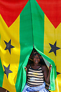 A woman working on her stall in the market, uses the national flag to shield her from the sun, Sao Tome<br /> Sao Tome and Principe, are two islands of volcanic origin lying off the coast of Africa. Settled by Portuguese convicts in the late 1400s and a centre for slaving, their independence movement culminated in a peaceful transition to self government from Portugal in 1975.