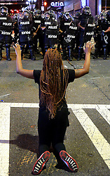 A protestor places her arms in the air while on her knees in front of Charlotte officers in riot gear at the intersection near the Epicentre in Charlotte, NC, USA, on Wednesday, Sept. 21, 2016. The protestors were rallying against the fatal shooting of Keith Lamont Scott by police on Tuesday evening in the University City area. Photo by Jeff Siner/Charlotte Observer/TNS/ABACAPRESS.COM