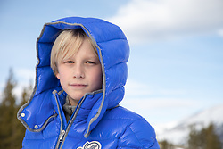 Blond boy in a blue hoody Winter coat