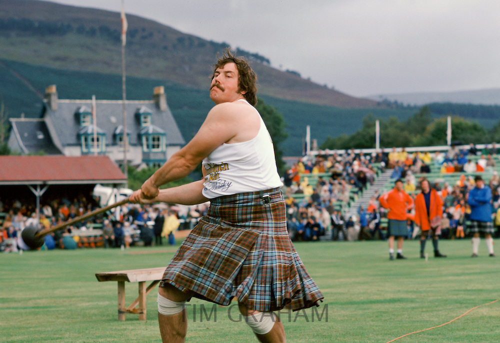 Scottish strongman in tartan kilt tossing the hammer at the Braemar Royal Highland Gathering, the Braemar Games in Scotland