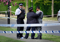 © Licensed to London News Pictures. 12/04/2017. London, UK. Police comfort a man standing inside the police cordon near Newnham Close where a 19 year old man, named locally as Abdullahi Tarabai,  was murdered yesterday after reportedly being chased though a housing estate in Northolt. This is the second fatal stabbing in the capital in 24 hours. The location is adjacent to a gun siege from October 2016. Four men have been arrested Photo credit: Peter Macdiarmid/LNP
