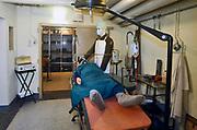 Nederland, Olst, 20-9-2017 Interieur van een commandobunker als onderdeel van de IJssellinie in de jaren 60 ten tijde van de koude oorlog tegen een aanval van Rusland, het warschau pact .. Affiche, poster, met tips om je te beschermen tegen de straling van een atoombom. Een telex, telexmachine voor verbinding met het hoofdkwartier staat rechts. Doel van het verdedigingswerk was bij een russische aanval het gebied tussen kampen en Nijmegen onder water te zetten,innunderen, om tijdwinst te boeken. Hiervoor waren op verschillende plaatsen inlaten gemaakt. Deze waren in de dijk gebouwd en konden geopend worden om het land binnendijks onder water te zetten. Kanonnen moesten deze inlaatplaatsen beschermen. Vrijwilligers hebben voor behoud van diverse objecten gezorgd. Foto: ANP/ Hollandse Hoogte/ Flip Franssen