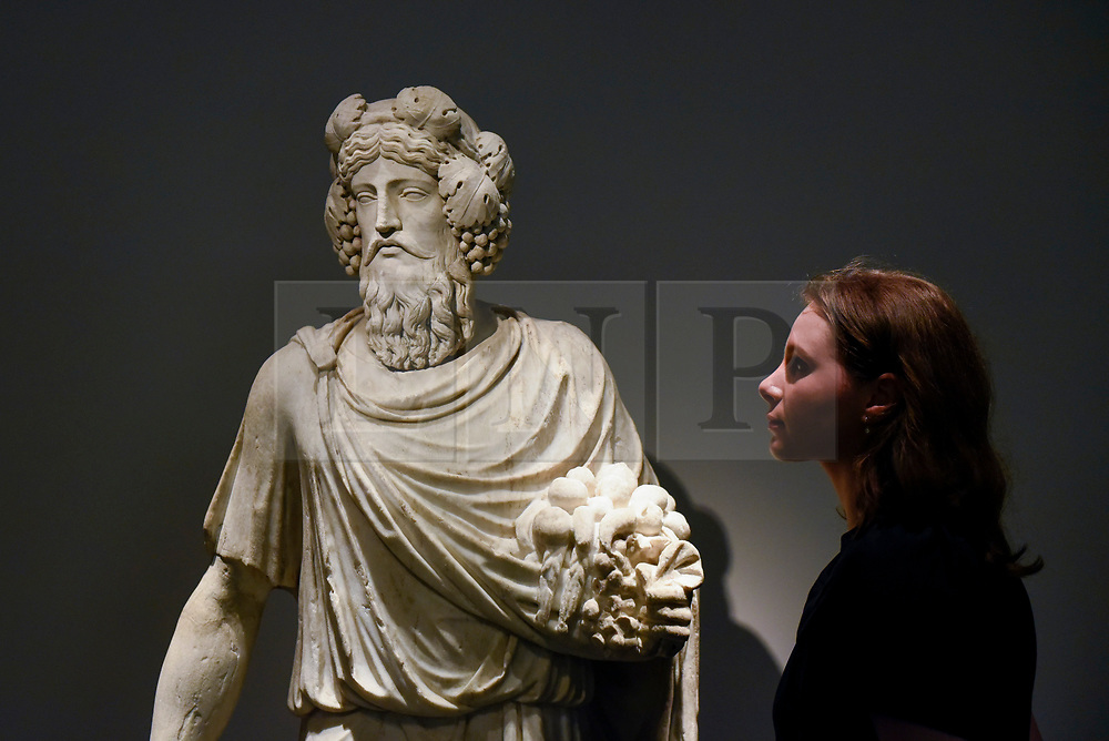 """© Licensed to London News Pictures. 25/06/2019. LONDON, UK. A staff member views """"Silvanus"""" a 1st century AD Roman marble scuplture, from Galerie Chenel at a preview of Masterpiece London 2019, the world's leading cross-collecting art fair held in the grounds of the Royal Hospital Chelsea.  The fair brings together 157 international exhibitors presenting works from antiquity to the present day and runs 27 June to 3 July 2019.  Photo credit: Stephen Chung/LNP"""