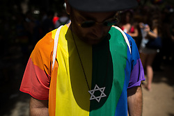 "© Licensed to London News Pictures . 03/06/2016 . Tel Aviv , Israel . A man wearing a large Star of David necklace and a rainbow t-shirt . Over 100,000 people attend the gay pride parade in Tel Aviv , reported to be the largest such event in the Middle East and Asia . The Israeli government has been accused of using the event as "" pinkwashing "" , marketing the event in order to deflect accusations of poor human rights behaviour . Photo credit: Joel Goodman/LNP"