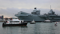 Portsmouth,Hampshire Wednesday 16th August 2017 HMS Queen Elizabeth arriving  at her home dock in Portsmouth  with onlookers catching a glimpse of the Royal Navy's £3billion flagship aircraft carrier as it passes along into Portsmouth Harbour. Many people took up there spots from the early hours of the morning to be part of the History in the making. The entry of the Ship was  accompanied by a flypast of Fleet Air Arm Merlin and Wildcat helicopters, plus Hawk jets of 736 NAS from Culdrose.<br /> <br /> Six tugs escorted the ship into harbour to assist  and manoeuvre the ship on to her berth in the naval base. Once the ship passes Outer Spit Buoy they are committed to entering harbour.<br /> <br /> <br /> Britain's newest aircraft carrier arrived just after 7.10am in her home dock after completing the latest round of sea trials. She arrived  a day earlier than previously expected, after weather conditions had formerly prevented the exact date from being set.<br /> <br /> The 65,000-tonne carrier, the largest warship ever to be built in Britain, is expected to be the Navy's flagship craft for at least 50 years.©UKNIP