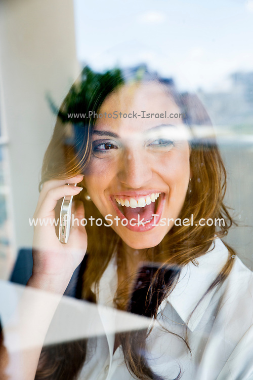 Successful young business woman reflects in her office window as she talks on a mobile phone