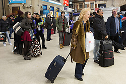 © Licensed to London News Pictures. 27/12/2013. London, UK. People wait for mainline trains at Victoria Railway station in London. Many National Rail services have been cancelled and disrupted as a result of very strong winds and rain. Southeastern Railways have cancelled all trains as a precaution until midday today and no rail services are running to Gatwick Airport this morning. Photo credit : Vickie Flores/LNP