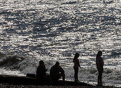 Licensed to London News Pictures. 23/09/2021. Brighton, UK. Sunbathers enjoy the sunny weather on Brighton beach, Sussex as weather forecasters predict warm autumnal weather to continue for the weekend with highs of 24c. Photo credit: Alex Lentati/LNP