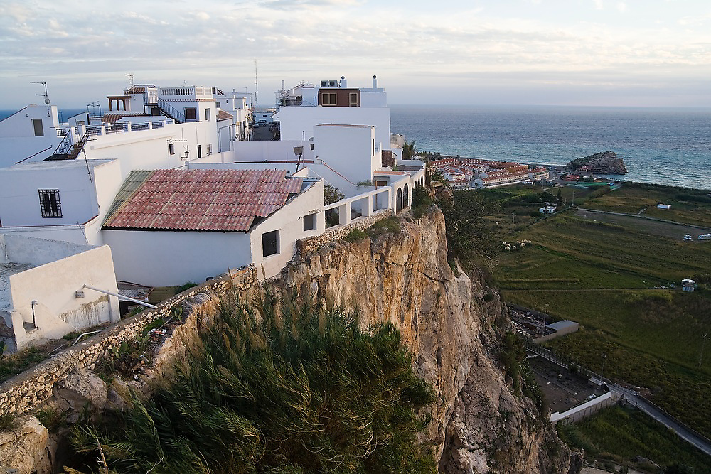 Whitewash buildings are perched on a cliff edge overlooking the coast of the Mediterranean Sea in Salobrena, Andalusia, Spain.