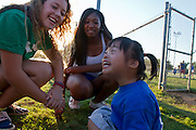Trina Yeoh, 6, has a laugh with volunteers Cristina Clawson (L) and Jessica Smith (R), students at McKinney Boyd HS during the Kiwanis Club of McKinney sponsored HALOS baseball game