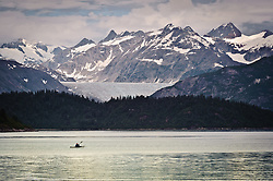 A kayaker paddles in Wachusett Inlet just off the Muir Inlet near Rowlee Point in Glacier Bay National Park and Preserve in southeast Alaska. Also pictured in the photo (back to front) is Black Mountain, Riggs Glacier, McConnell Ridge and Westdahl Point.