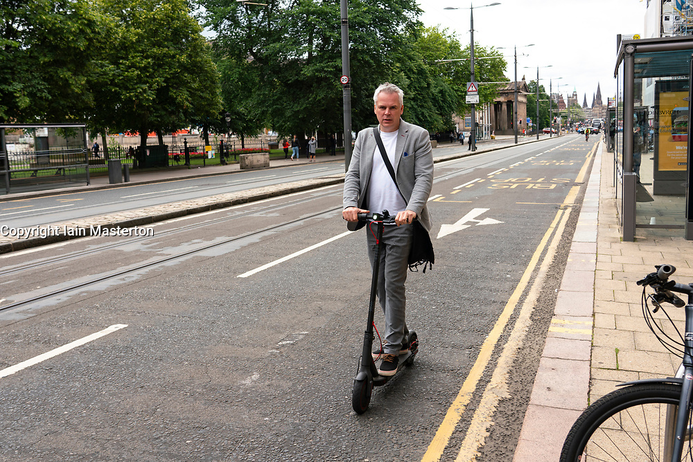 Edinburgh, Scotland, UK. 2 July, 2020. A man using an electric scooter to travel along Princes Street in Edinburgh. Government is to allow trials on public roads of electric scooters this month. Currently their use is banned. Iain Masterton/Alamy Live News