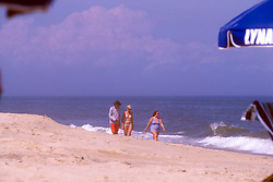 Unidentified beachcombers walk along the ocean, Friday, Aug. 16, 2019 at Henlopen Acres Beach Club in Rehoboth Beach, Del. (Photo by D. Ross Cameron)