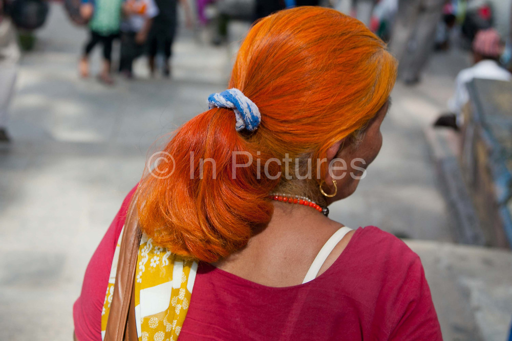 A woman with died orange hair at a Buddhist festival below the Swayambhunath temple complex, also called the Monkey Temple.