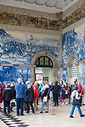 Tourists admiring famous azulejos traditional Portuguese blue and white wall tiles Sao Bento railway station in Porto, Portugal