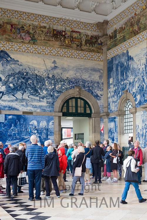 Tourists admiring famous azulejos traditional Portuguese blue and white wall tiles Sao Bento railway station in Porto, Portugal