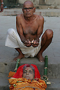 Gopal Jee Singh, 65, from Bihar, holds a butter lamp above his dead wife Subhadra Singh, 60 for a local photographer who takes photographs at the burning ghats and sells prints to families that want a keepsake. Subhadra died last night at 8 p.m. and he and his sons brought her here to Varanasi for the funeral rite, arriving at 3 a.m..Mr. Singh says that his wife didn't want to be cremated and so he and their sons brought her here to the Ganges for a different funeral ritual then most others have.
