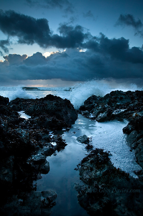 From stormy weather, wind waves and surf crash over rocks into a rockpool at sunset at this rocky point at Porth Tyn Tywyn, Rhosneigr, West Anglesey.