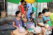 Vendors at an early morning street market in Yangon, Myanmar on 18th May 2016.  A large variety of local products are available for sale in fresh markets all over Yangon, all being sold on small individual stalls