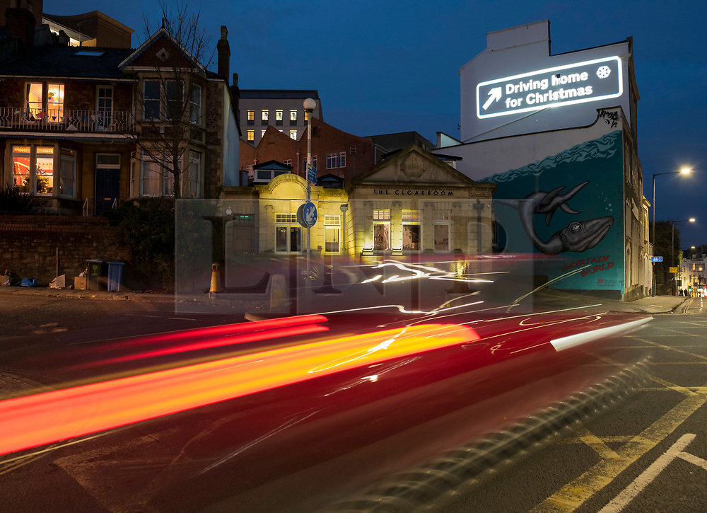 "© Licensed to London News Pictures; 09/12/2020; Bristol, UK. Car light trails created by a long camera exposure are seen as the words ""Driving Home for Christmas"" are projected onto a building on Park Row in Bristol during the Covid-19 coronavirus pandemic in England. With England under a three-tier system advising against travel it is expected that there will be a lot of traffic just before Christmas when Covid restrictions are lifted and people can travel to visit friends and relations for Christmas. The projection is part of a series for ""Bristol ADVENTures"", a new arts project spearheaded by Bristol City Centre BID. This sees a new building lit each day with a selection of the most jolly and iconic Christmas lyrics, with a trail of 24 locations complete by Christmas Eve. Photo credit: Simon Chapman/LNP."