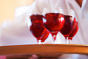 A waiter in white coming with a tray of glasses with Kir aperitif bright red translucent, in motion blurred unsharp, colourful, made by mixing white wine, traditionally Burgundy Aligote, with black currant (called cassis in French) liqueur Cassis Cote d'Azur Var France Bouches du Rhone