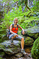 An athletic woman posing for a portrait on a rocky path amongst moss covered rocks, Little Si trail, Washington, USA.